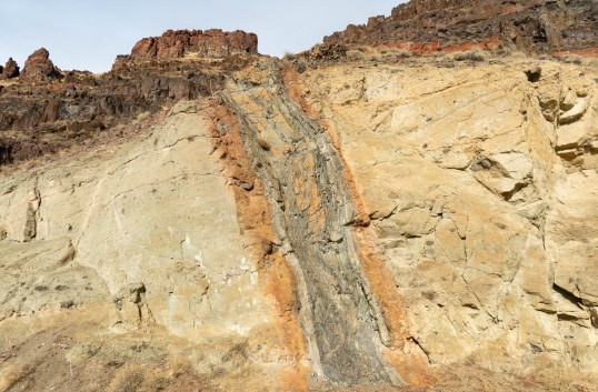 Basaltic dike intruding volcanic mudflow deposits, eastern Oregon. Note the baked and altered edge of the country rock.